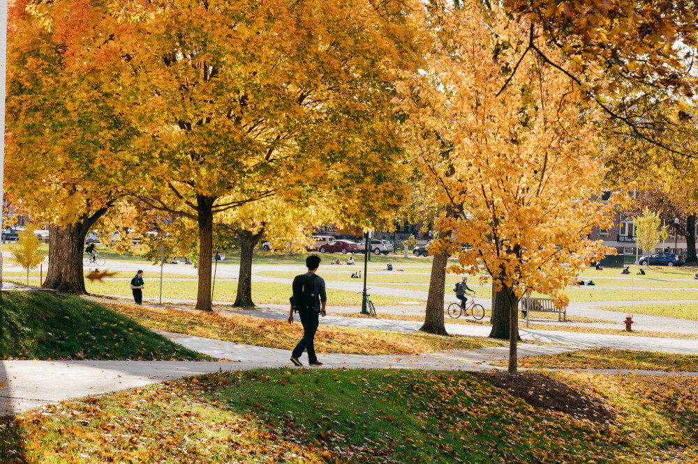 Student walking on Dartmouth campus with fall foliage