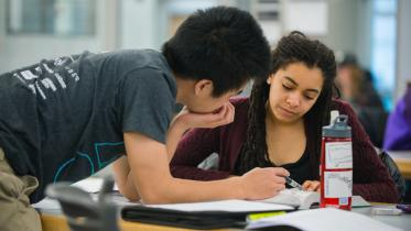 Two students studying at a table.