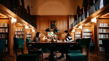 Two students studying at a table in Baker Library.