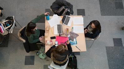 A group of four students studying at a table.