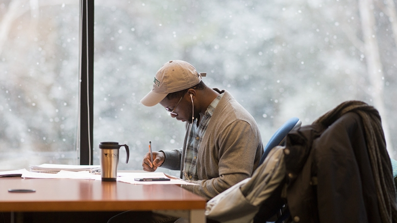 Student studying by window in snow.