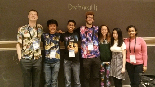 six students standing together in front of a blackboard with Dartmouth written on it in chalk