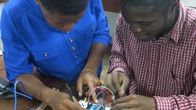 two students building a circuit board