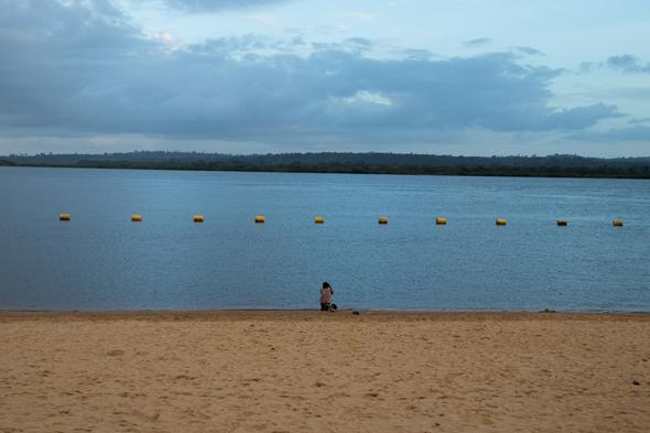 A woman looks out on the Xingu River.