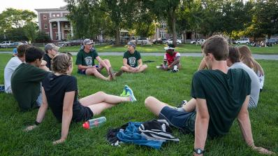A group of students sit in a circle outside.