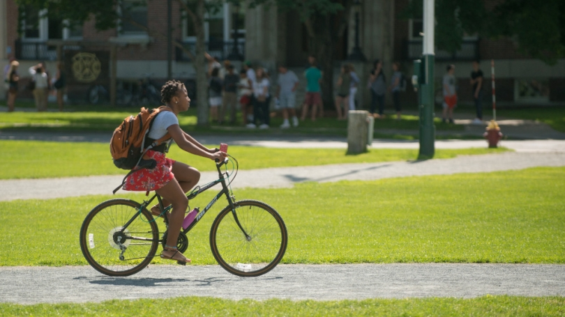 A student rides their bick across the Dartmouth Green.