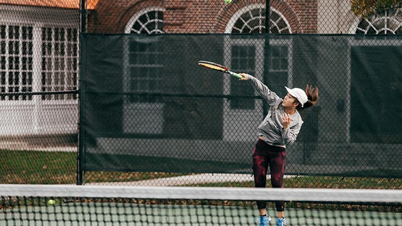 A student serves a tennis ball on the tennis court.