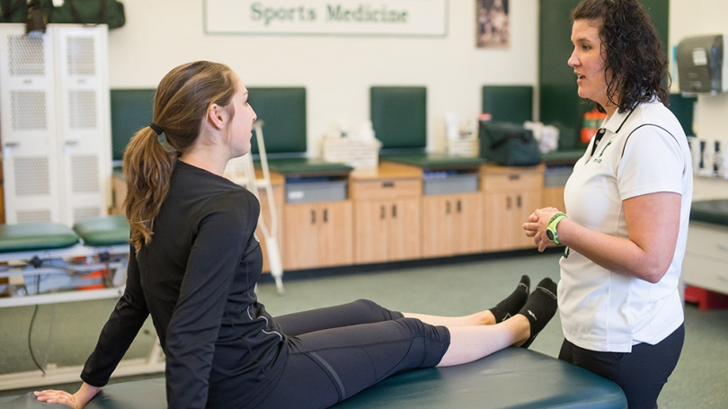 An athletic trainer works with a student-athlete on a massage table.