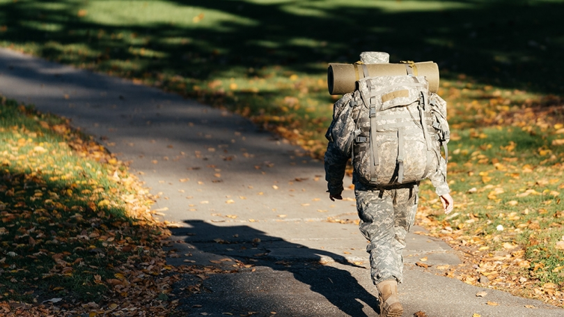 A ROTC student walks in the foliage with a backpack.