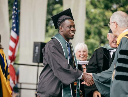 Theo Wilson shaking hands with President Phil Hanlon during Commencement.