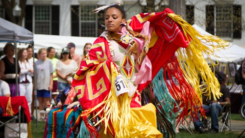 a dancer wearing colorful traditional Native American dress