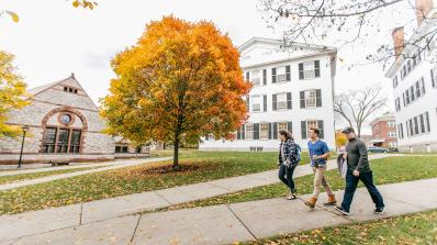 Student walk on campus sidewalks during fall foliage.