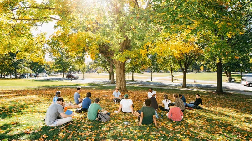 Student in class under a tree during fall.