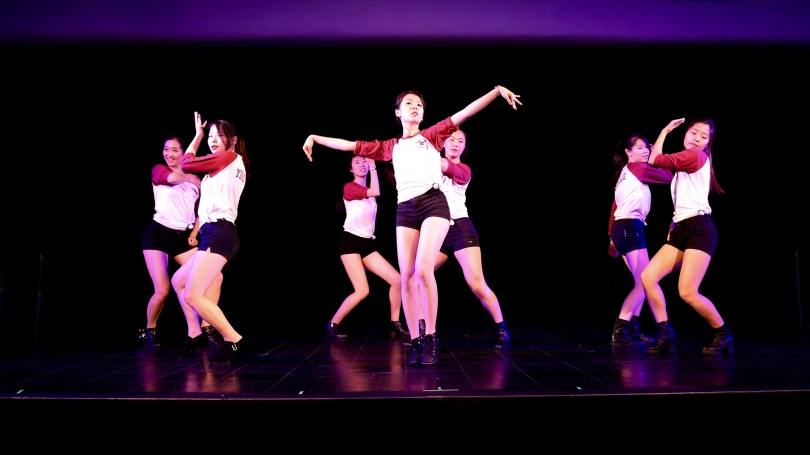 Students perform a dance on stage.