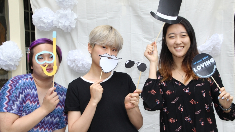 Three students pose in a photo booth with props.
