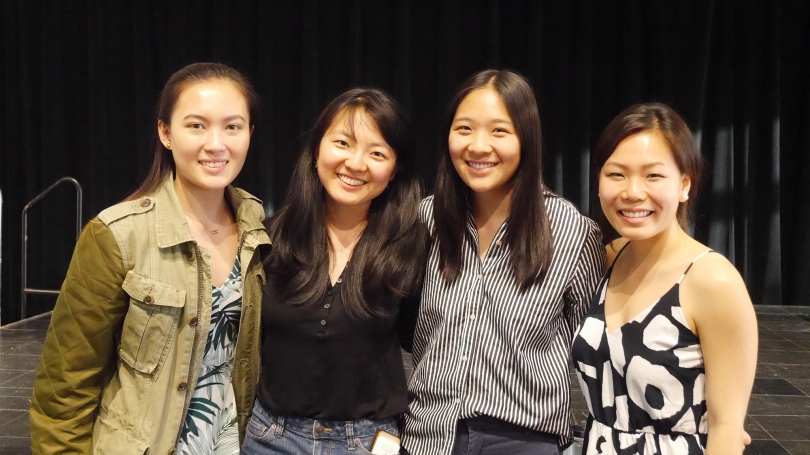 Four students smile on stage together.
