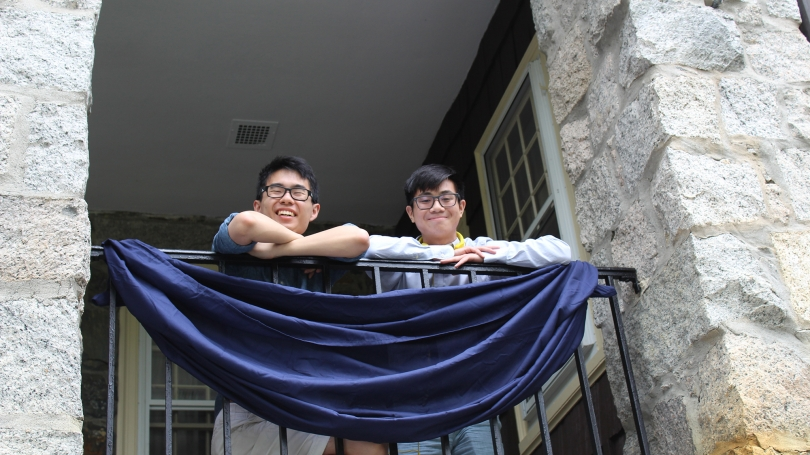 Two students smile down from the balcony.