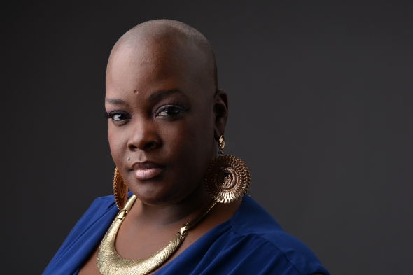 Sonya Renee Taylor wearing a blue shirt, gold earrings, and a gold necklace and looking into the camera