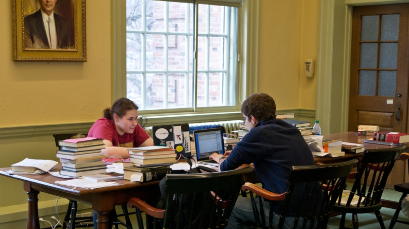Two students sitting and studying with their books and computers.
