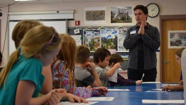 A Dartmouth student talks with young students in a classroom.