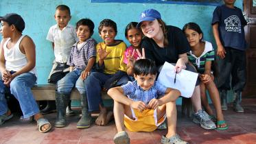 A student posing with local children