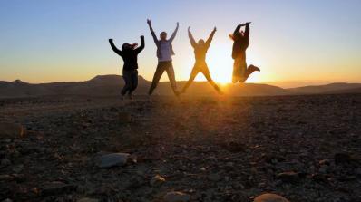 Students jumping at sunrise.