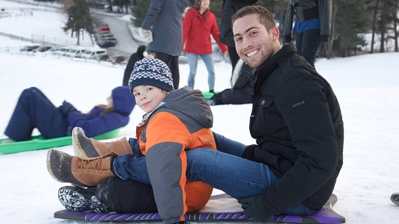 A student and a child sled during an outing.