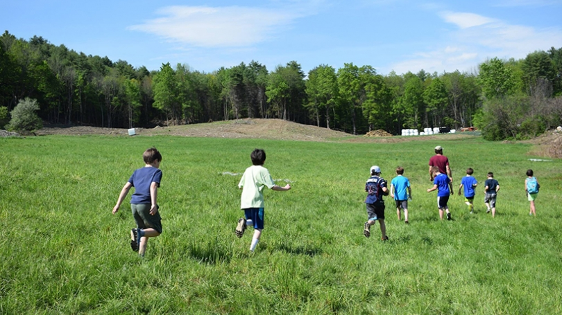 Kids and students running through a field