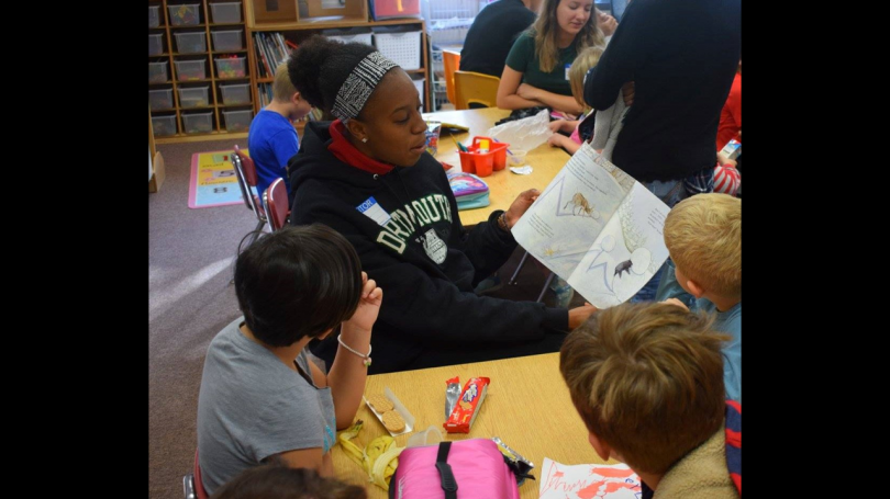 America Reads Mentor reads to a group of kids during snack time in a classroom