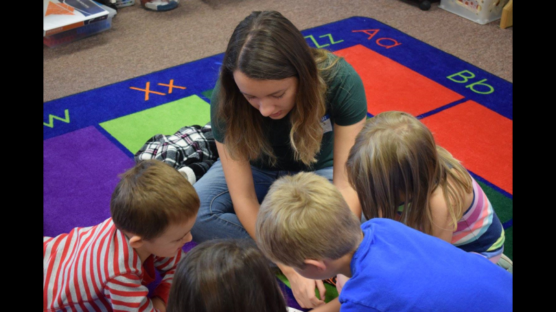 Dartmouth mentor reads with a group of kids in classroom