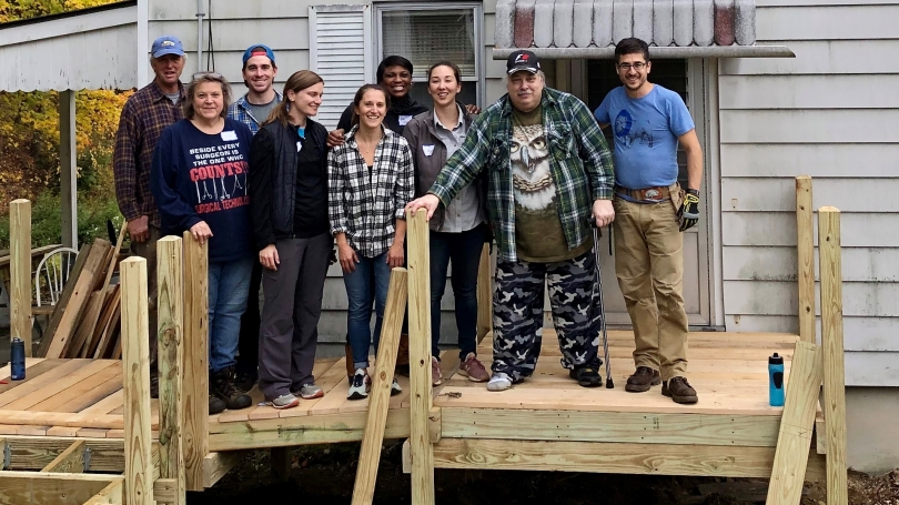 Group of students and home owner standing together on newly built deck outside of home