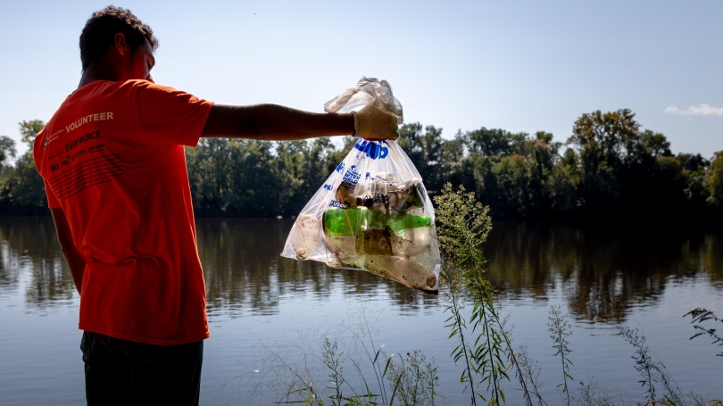 Student standing beside river with bag of trash