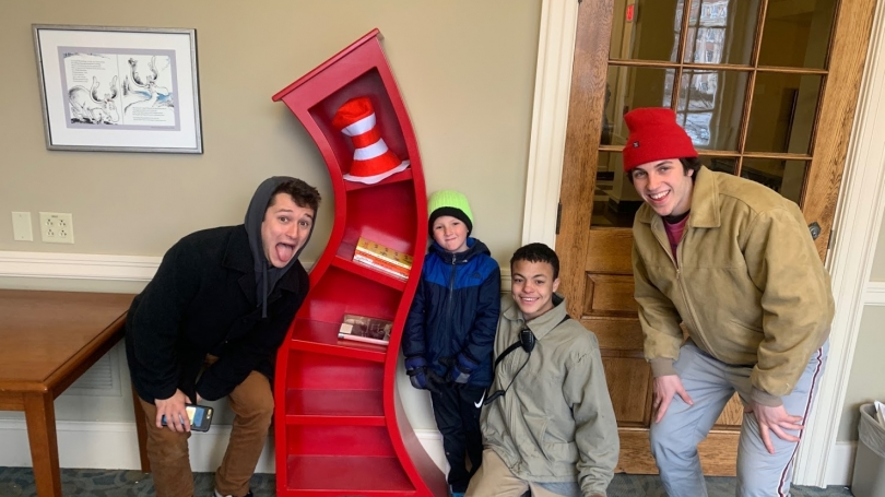 Two mentors and two mentees pose for a picture with the Dr. Suess shelf in Baker-Berry Library