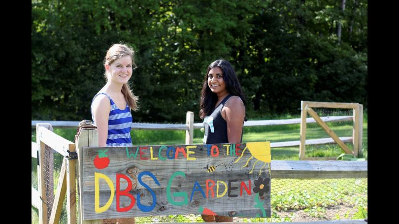 Two mentors standing in the garden behind DBS Garden sign