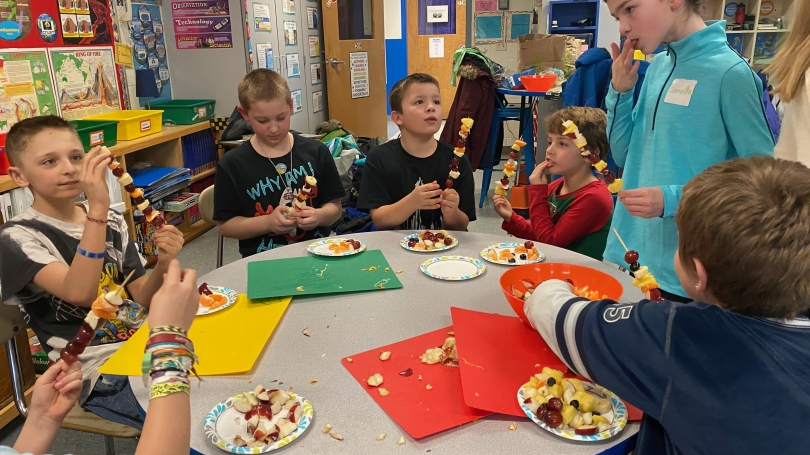Group of Growing Change students and mentor in a classroom enjoying a snack after school