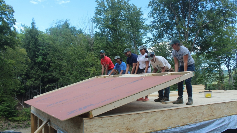 Students volunteering with Habitat for Humanity erecting structure