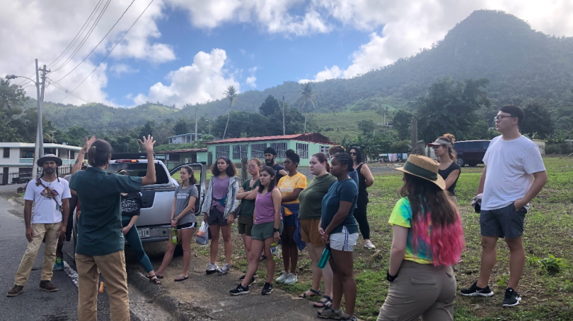 Group of students road side in front of mountains receiving instructions