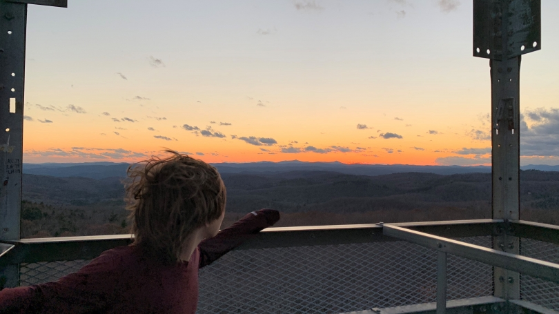 Student participant at the top of a fire tower looking out at sunset