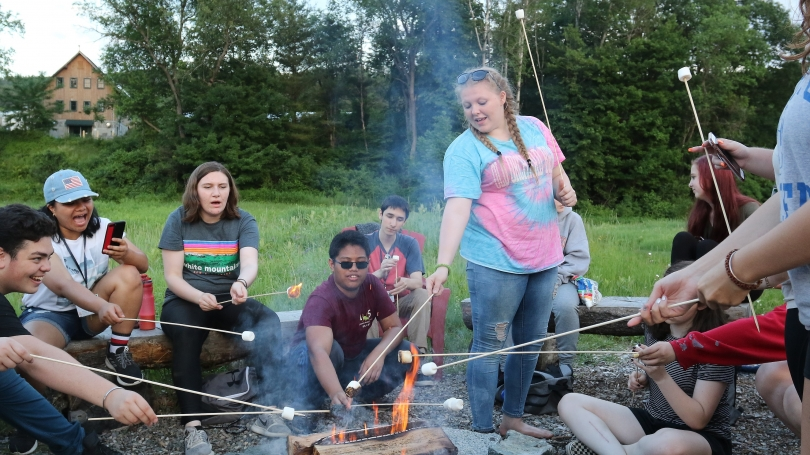 Group of students making s'mores around bonfire in a field