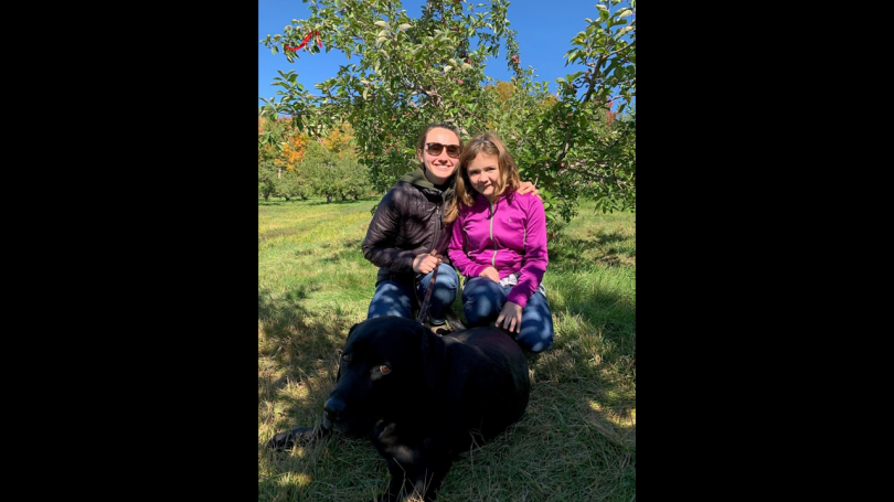 Outdoor image of trees and field with black dog and two people