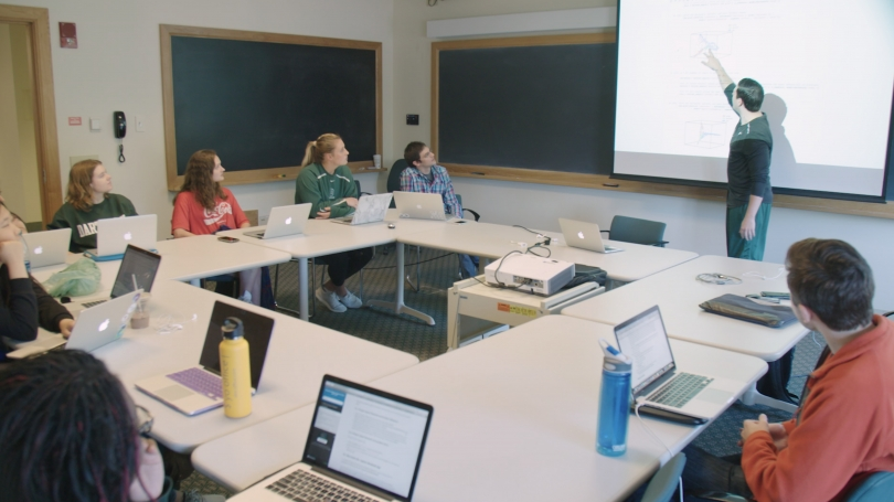 Students in a classroom watch a professor lecturing at the whiteboard.
