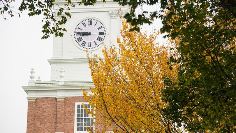 Close-up photo of Baker Clock Tower with yellow and green leaves in the foreground