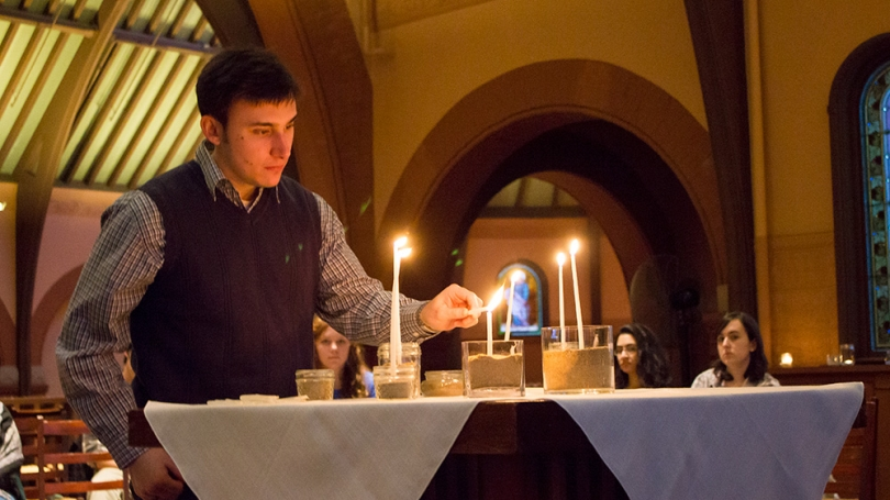 A student lights a candle during the Sunday Service at Rollins Chapel.