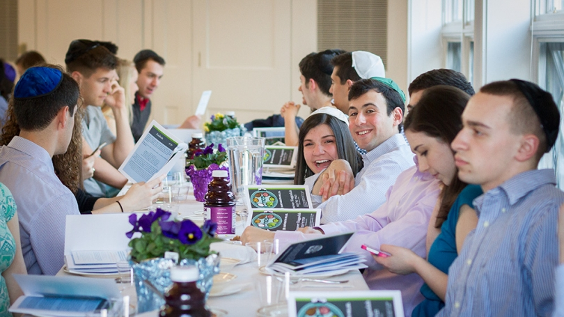 A group of students sitting together at a table at the Roth Center for Jewish Life.