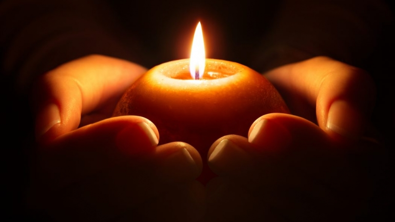 Lit candle being held by hands