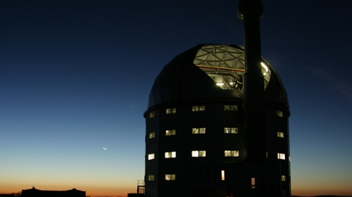 a silhouette of an observatory building against a sunset sky