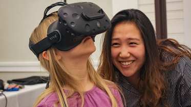 a woman watching another woman testing a virtual reality device