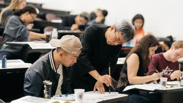 A professor works with a student doing Chinese calligraphy.