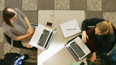 Two students studying at a table in the library.