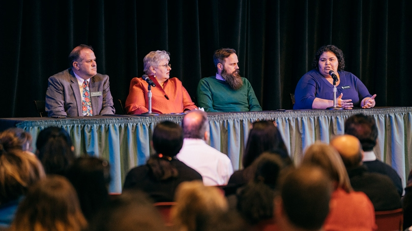 Four deans sit on stage at a panel table.